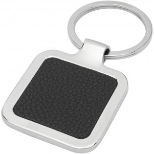 Quadratischer Schlüsselanhänger in Premiumqualität aus schwarzem PU-Leder mit Metallgehäuse aus Zink Legierung, geliefert in einem braunen Papierumschlag. Die Größe des Schlüsselanhängers beträgt 4 x 5 cm. Hergestellt für Lasergravur, wodurch das Logo in Silber erscheint.
